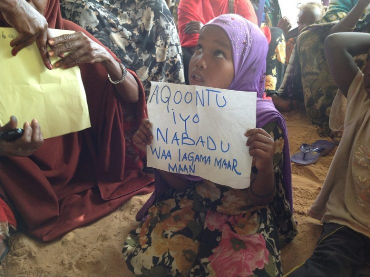 "Young IDP girl holding paper written with ""Its necessary to have peace and education"""